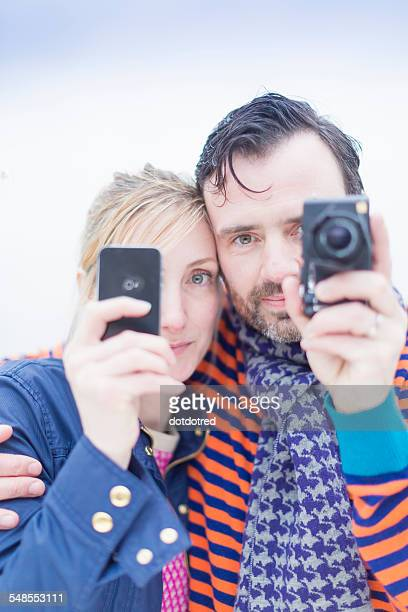 Couple taking photographs with smartphone and camera