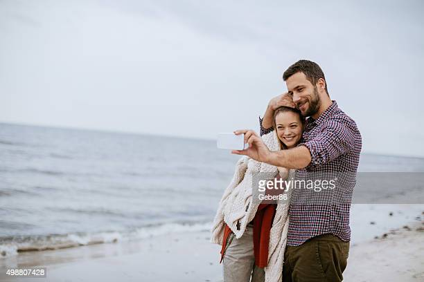 Couple taking photos at the beach