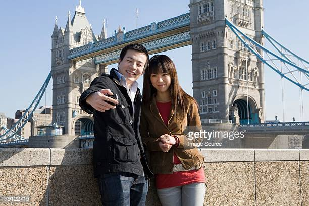 Couple taking picture by tower bridge