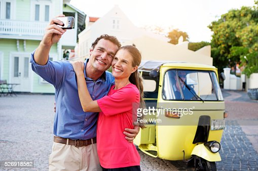 Couple taking picture in front of tuk tuk : Stock Photo