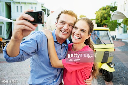 Couple taking picture in front of tuk tuk : ストックフォト