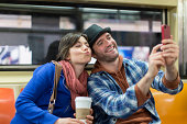 Couple taking picture on subway