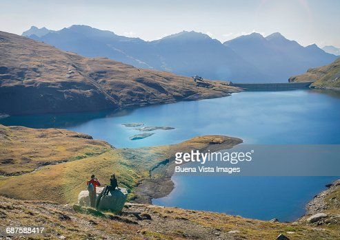 Couple taking pictures near an alpine lake