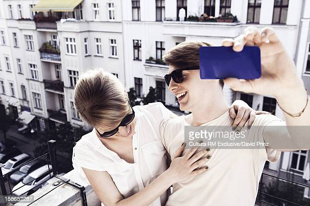 Couple taking pictures on city balcony