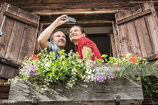 Couple taking self portrait from chalet window, Achenkirch,  Tyrol, Austria