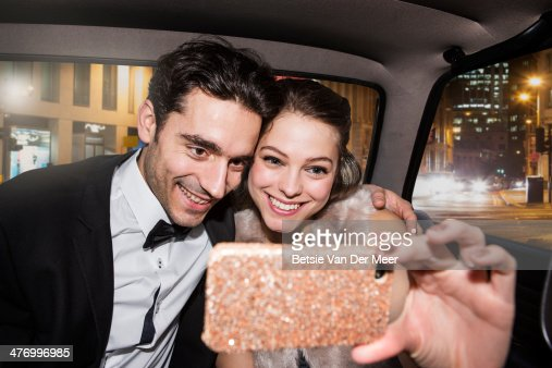 Couple taking self portrait on phone in car.