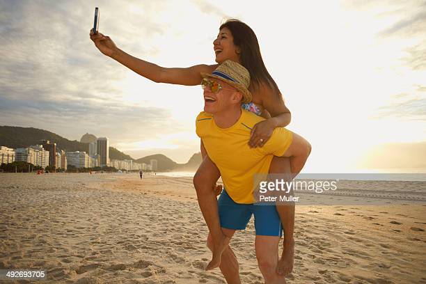 Couple taking self portrait on smartphone, Copacabana beach, Rio De Janeiro, Brazil