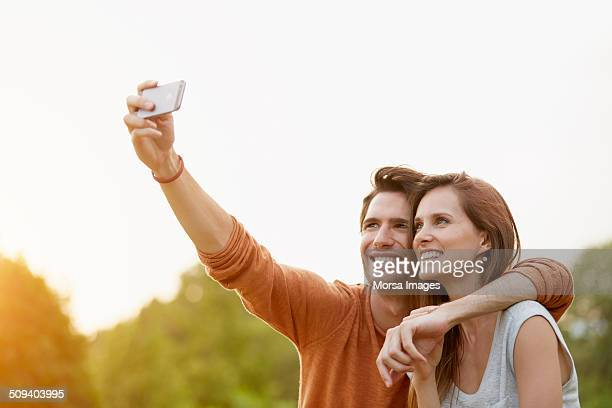 Couple taking self portrait through mobile phone