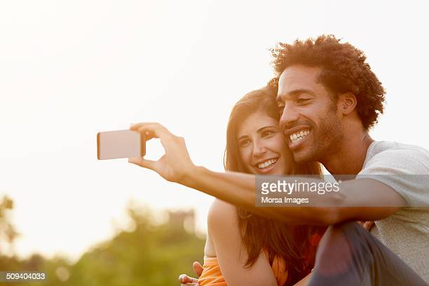 Couple taking self portrait through mobile phone