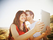 Couple taking self portrait with digital tablet