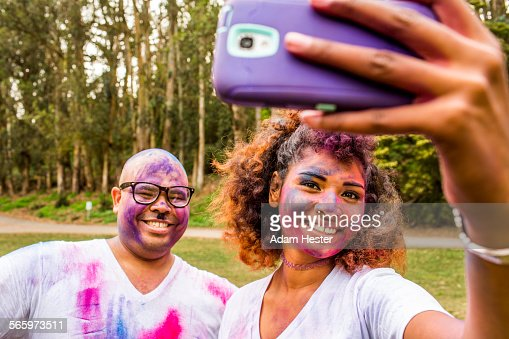 Couple taking selfie covered in pigment powder