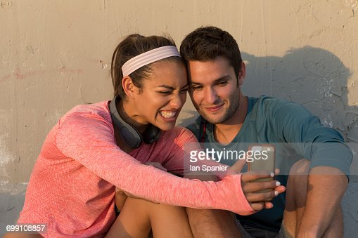 Couple taking selfie in front of concrete wall