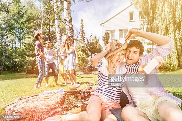 Couple taking selfie on picnic blanket