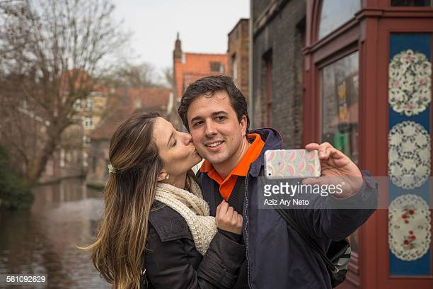 Couple taking selfie on smartphone, Bruges, Flanders, Belgium