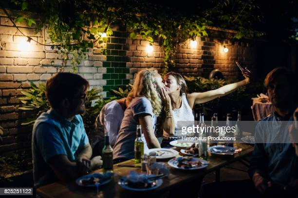 Couple Taking Selfie While Kissing At Barbecue With Friends