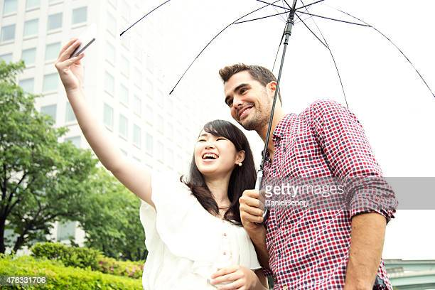 Couple Taking Selfie With Smart Phone Outdoor on Rainy Day