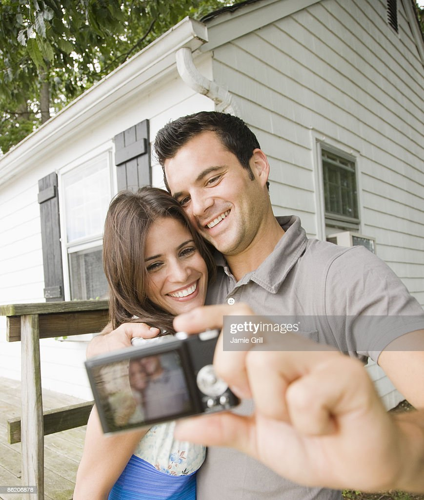 Couple taking self-portrait in front of house
