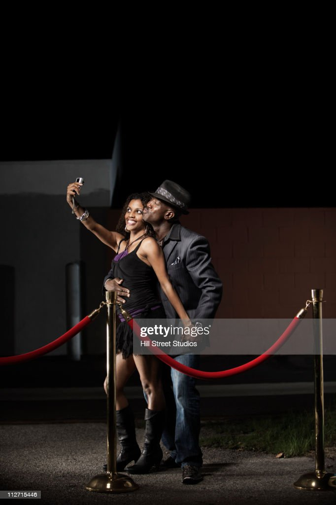 Couple taking self-portrait while standing in line : Stock Photo