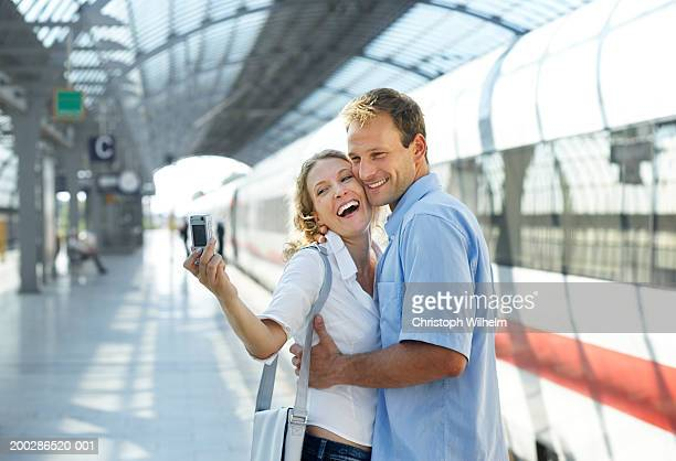 Couple taking self-portrait with digital camera at train station