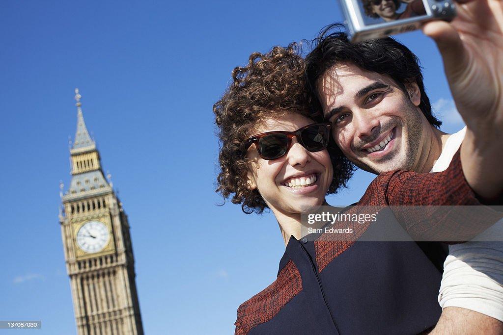 Couple taking self-portrait with digital camera below Big Ben clocktower in London : Stock Photo