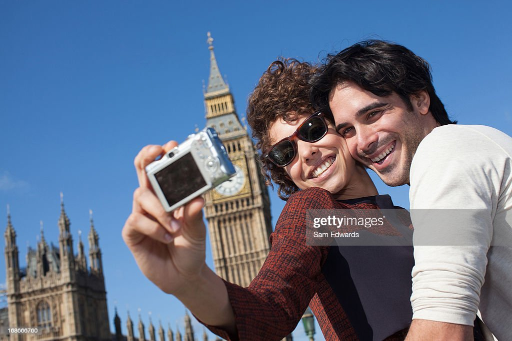 Couple taking self-portrait with digital camera below Big Ben clocktower in London : Stock Photo