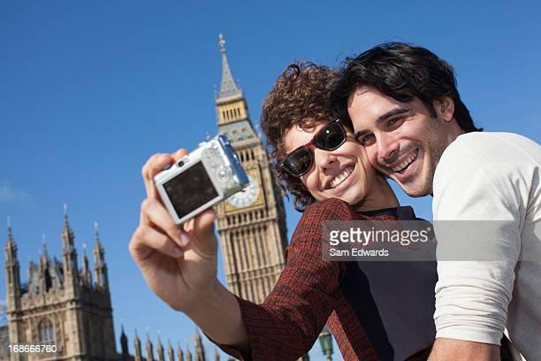 Couple taking self-portrait with digital camera below Big Ben clocktower in London
