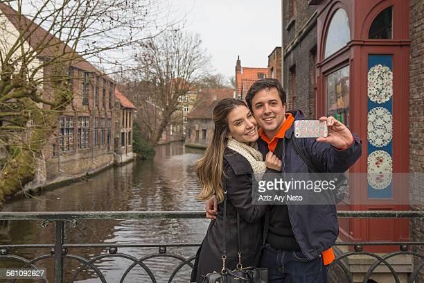 Couple taking smartphone selfie, Bruges, Flanders, Belgium