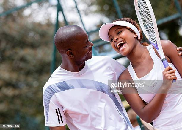 Couple taking tennis lessons