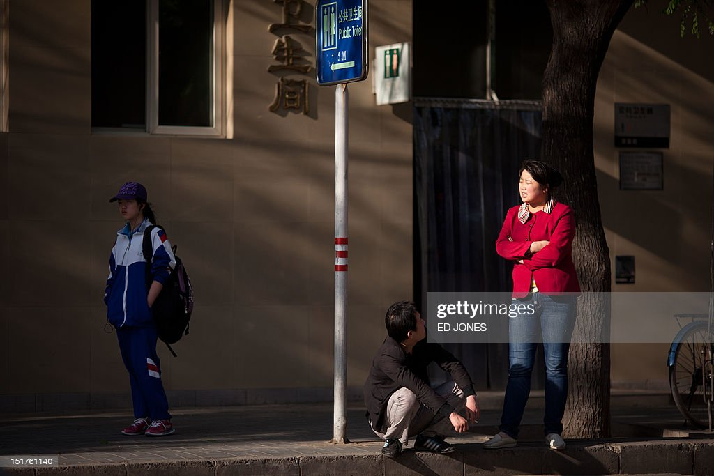 A couple talk as they wait on a street in Beijing on April 25, 2012. China's economy is widely expected to slow this year as woes in key export markets such as Europe and the United States hit its overseas sales, according to a report released by HSBC on April 23. AFP PHOTO / Ed Jones