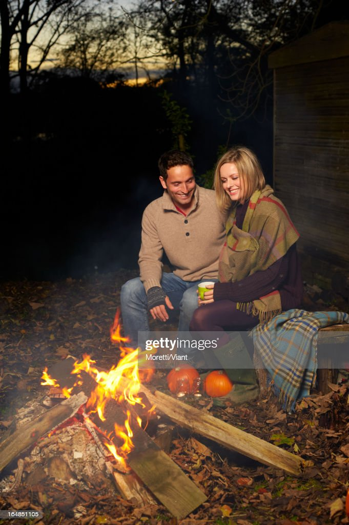 Couple talking around campfire at night : Stock Photo