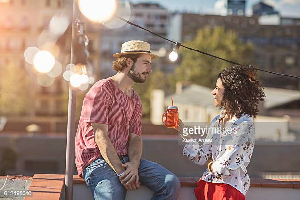 Couple talking at sunset on a rooftop party
