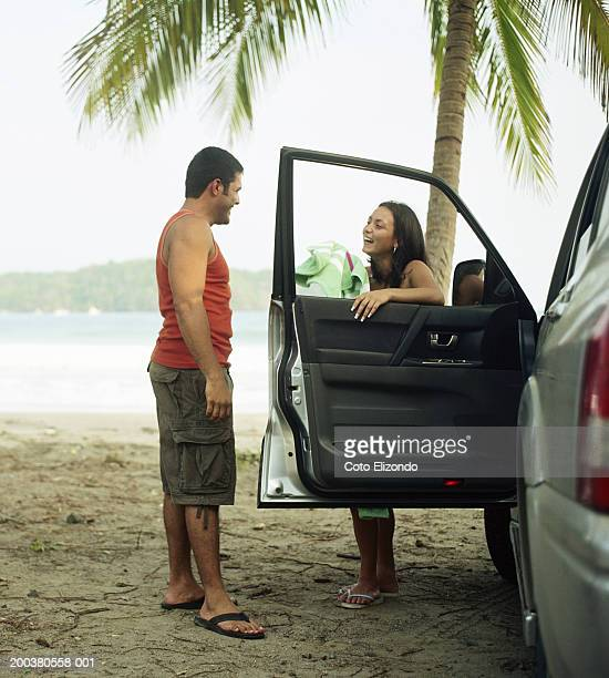 Couple talking by car at beach