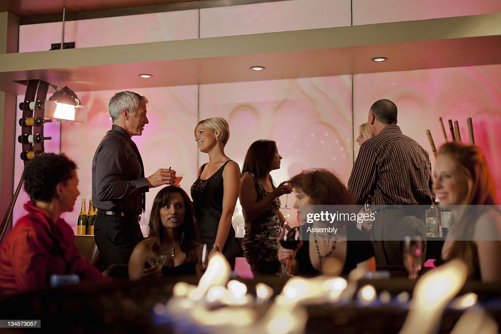 Couple talking in a busy cocktail lounge. : Stock Photo