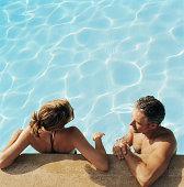 Paar in Unterhaltung im pool, entspannen Sie auf der Seite der Wand, erhöhten Blick