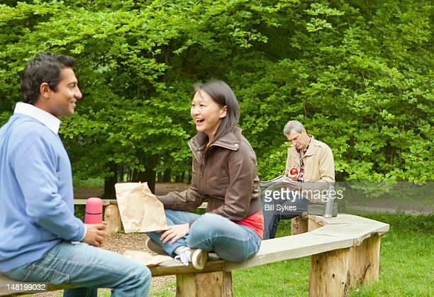 Pareja hablando en mesa de madera en el parque