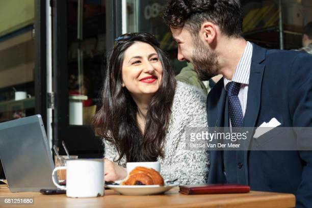 Couple talking sitting in pavement cafe having coffee and croissants