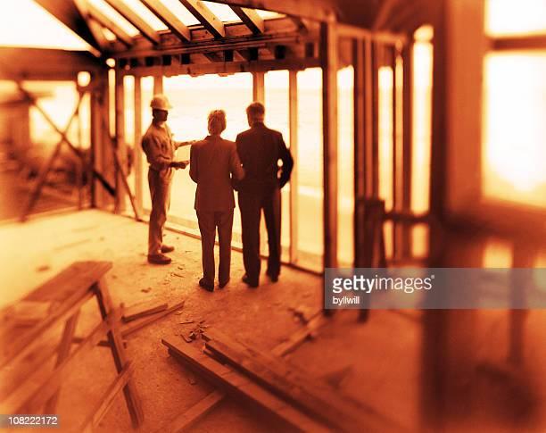 Paar im Gespräch mit Bau Arbeiter im Rahmen des Hauses
