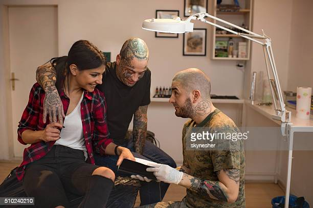 Couple talking to tattoo artist and looking at tattoo catalog.