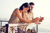 Couple talking while having spritz in a lake view terrace in summer