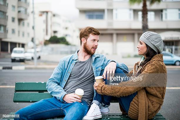 Couple talking while relaxing on bench by street