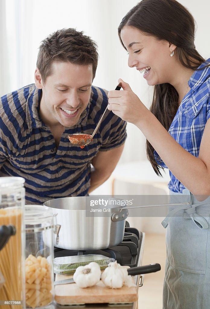 Couple Tasting Tomato Sauce : Stock Photo
