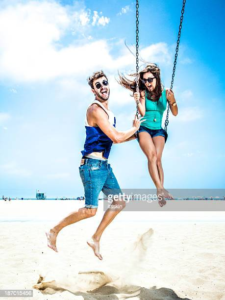 Couple teetering on swings LA beach