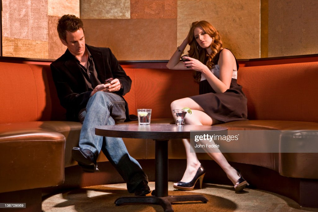 Couple text messaging in nightclub