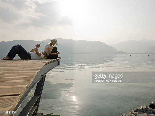 Couple text & use digital tablet on lake wharf