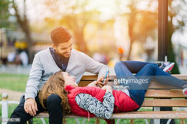 Couple texting on smartphone in the park