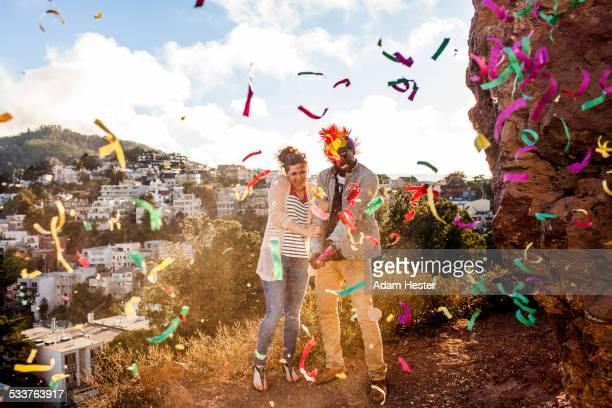 Couple throwing confetti on hill overlooking cityscape