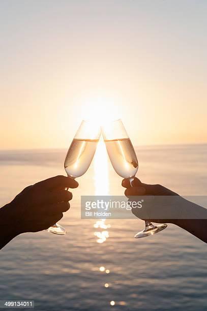 Couple toasting against sunset