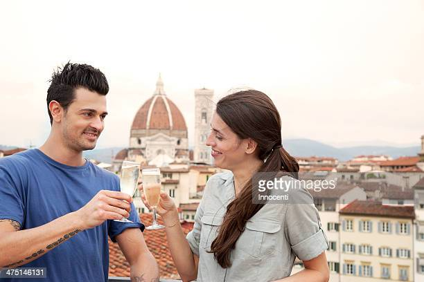 Couple toasting champagne, Florence Cathedral in background, Florence, Tuscany, Italy