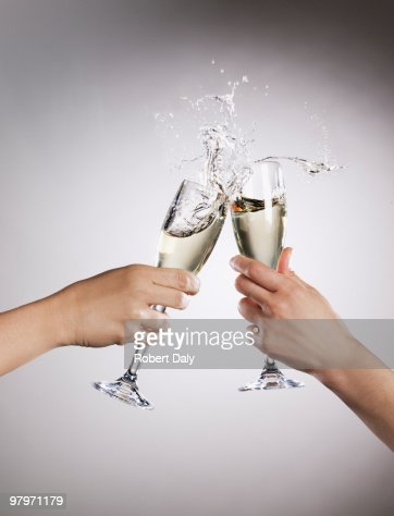 Couple toasting champagne flutes and spilling