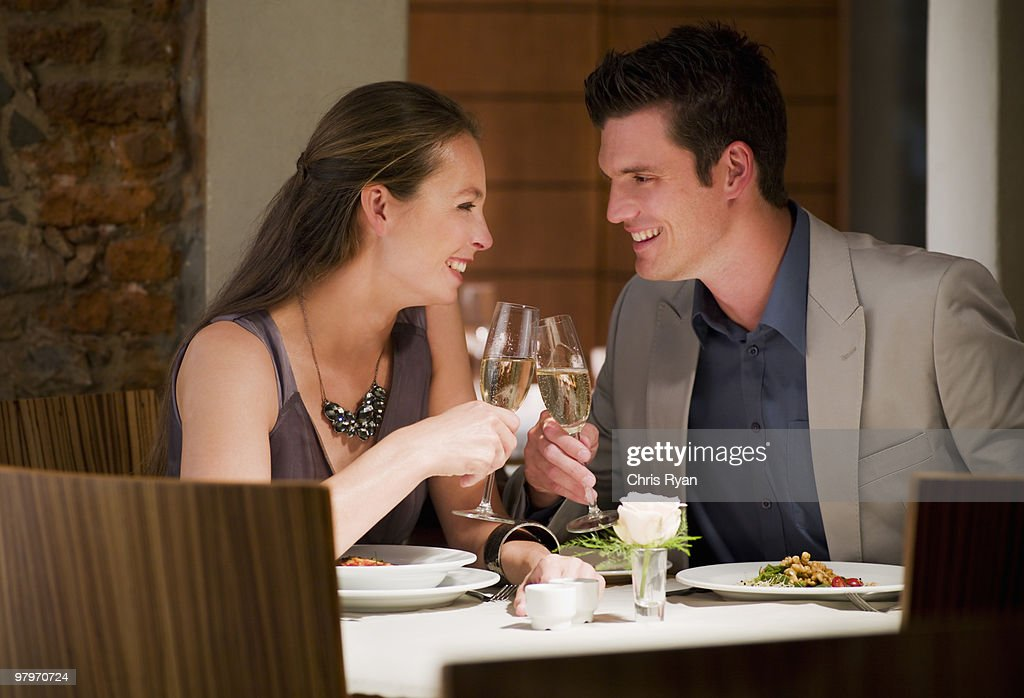 Couple toasting champagne glasses at restaurant table